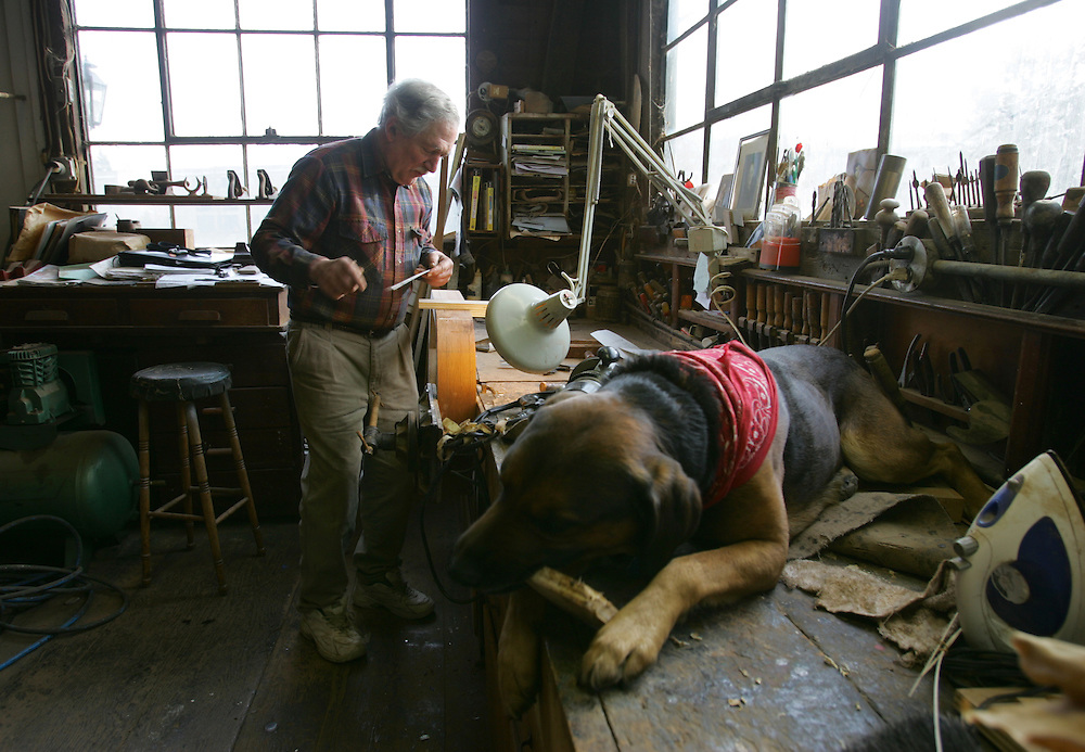 """Braintree, MA 02/05/2010<br /> John Sullivan crafts a coffee table from mahogany in his workshop as his dog Mickey does some woodworking of his own on Friday afternoon.  Sullivan said he decided decades ago that he would switch careers from the business world and start working in his uncle's ship building shop overlooking the Monatiquot River.  Some 25 years later, he is the man behind Starling Furniture, a successful fine furniture shop in the East Braintree/Weymouth Landing area.  """"It's interesting work,"""" Sullivan says, """"You get hooked on it.""""."""