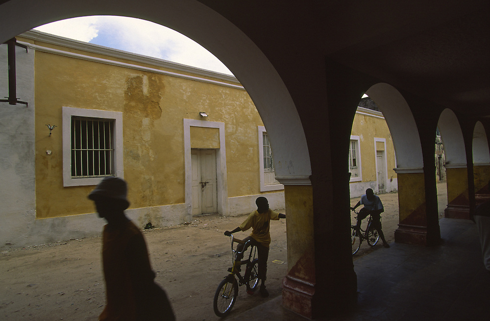 Children drive their bycicles in Arches Street, one of the most beautiful streets in Ilha de Mozambique