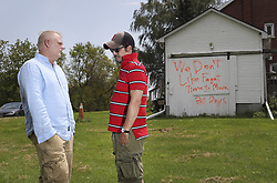 August 2, 2017 - Pickering, Ontario, Canada - PICKERING, ON - AUGUST, 2  . ''We don't like fagots (sic). 30 days. Time to move.'' Paul Alford-Jones (left) and his husband Brett Alford-Jones (cap and glasses) found this homophobic graffiti sprayed in orange paint on their garage in Pickering Tuesday evening. The couple, who have a five-year-old daughter, live in north Pickering..August, 2 2017  Richard Lautens/Toronto Star (Credit Image: © Richard Lautens/The Toronto Star via ZUMA Wire)