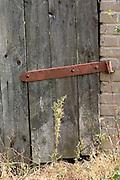Door with large rusty hinge on polish farm.  Zawady   Central Poland