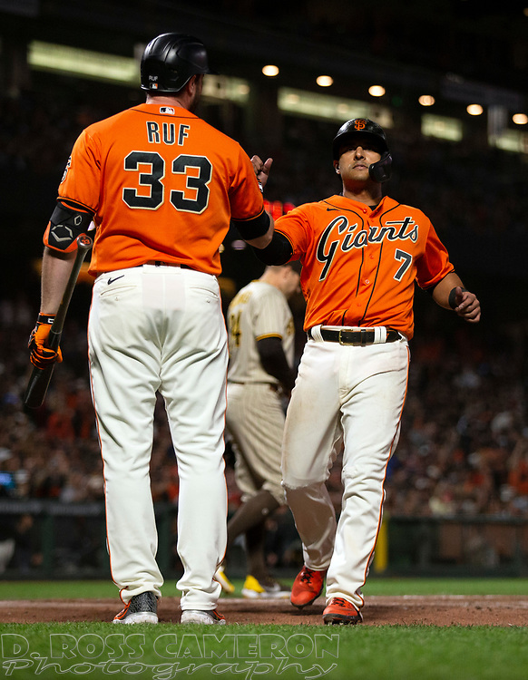 Oct 1, 2021; San Francisco, California, USA; San Francisco Giants second baseman Donovan Solano (7) is greeted by teammate Darin Ruf (33) as he scores on a sacrifice fly by LaMonte Wade Jr. during the sixth inning against the San Diego Padres at Oracle Park. Mandatory Credit: D. Ross Cameron-USA TODAY Sports