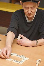 Deaf man with learning disabilities playing dominoes at a resource for people with physical and sensory impairment.