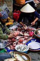 Two women prepare fish for sale in an old quarter market in Hanoi, Vietnam.