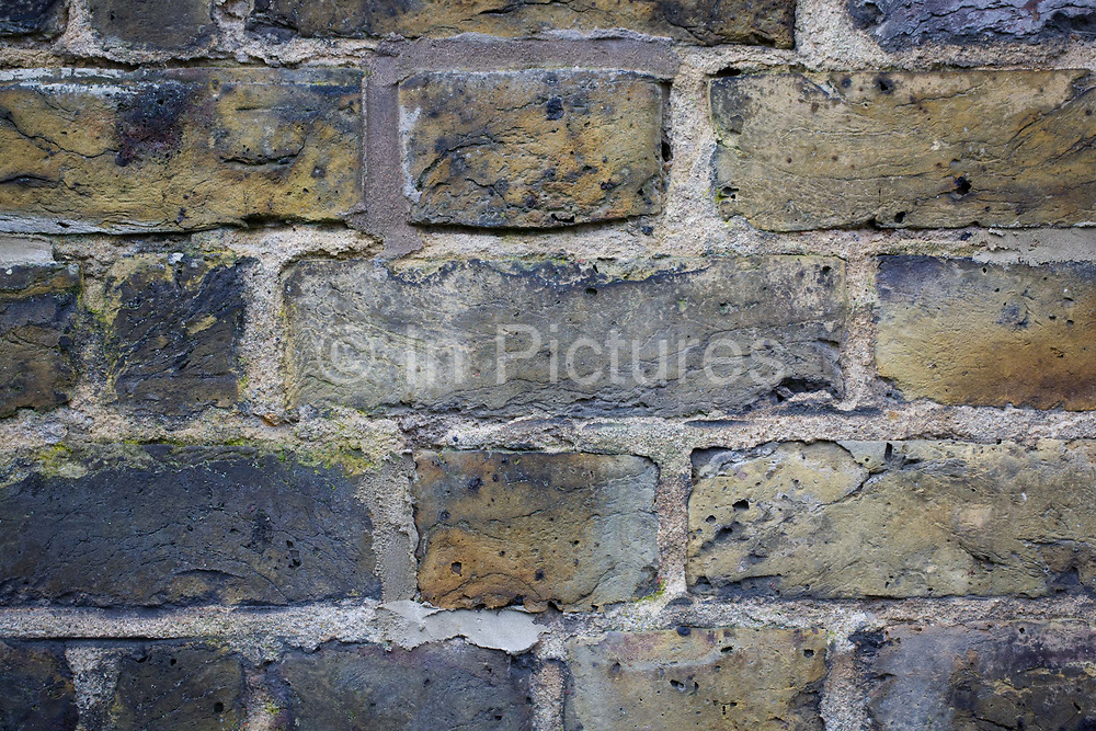 Detail of yellow London brick stock laid in English Garden Bond on a south London Edwardian house. Rows of brick and cement, known as mortar are laid in courses called bonds and here, this style of ordering them is specifically, Sussex Bond. The stock of brick is London Stock, a yellowish colour favoured by Victorian and Edwardian buildings in the south-east of England. This was made locally in Suffolk and Kent and transported up-river on stumpies or brickies - kinds of Thames sailing barges. But bricks and mortar is also a metaphor for home ownership and in the economic sense, the value and security of investing in property.