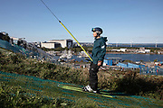 A ski instructor rises up using the T-Bar lift with Copenhagen harbour in the background.