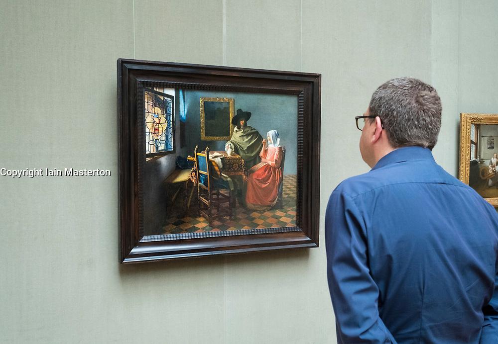 Man looking at painting by Johannes  Vermeer , The Glass of Wine ,at Gemaldegalerie museum, at Kulturforum in Berlin, Germany