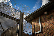 Razor wire sits on top of large metal security gates of an internal security fence that surrounds a Prison Wing of HMP Pentonville, London, UK.  The windows of individual cells can be seen through the fence. (Photo by Andy Aitchison)