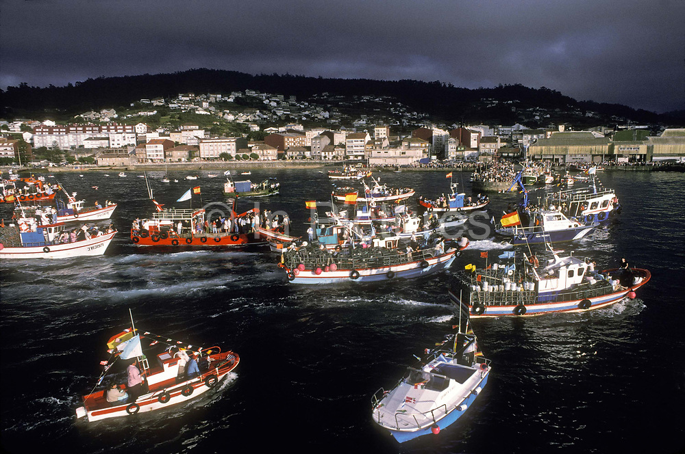 """Once a year in mid July, many of the large and small fishing communities across Spain celebrate the Patron Saint to Fishermen, """"Nuestra Señora del Carmen"""". The Patron saint is loaded onto a boat and a flotilla  of the town's fishing and leisure boats head out to sea with  local dignitaries and  the local priest. Seen here the fleet returning to harbour, Bueu, Galicia, Spain"""