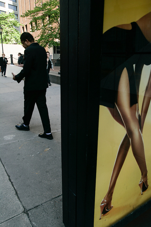 A man passes by an advertising of ladies stocking.