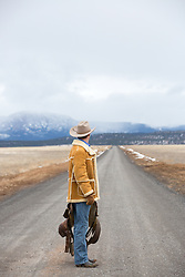 cowboy standing on a  dirt road with a saddle looking at a mountain