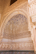 "Ornate architectural artwork on courtyard walls of Nasrid Palace. Arabesque arches and fine carvings adorn this finely-detailed Moorish architecture. This is the Patio de los Arrayanes (Court of the Myrtles), also called the Patio de la Alberca (Court of the Blessing or Court of the Pond), from the Arabic birka, ""pool"". There are galleries on the north and south sides; the southern gallery is 7 m (23 ft) high and supported by a marble colonnade. Underneath it, to the right, was the principal entrance, and over it are three windows with arches and miniature pillars. From this court, the walls of the Torre de Comares are seen rising over the roof to the north and reflected in the pond. The Alhambra's Moorish palaces were built for the last Muslim Emirs in Spain and its court, of the Nasrid dynasty."