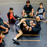 Young wrestlers watch a demonstration from Gallup High School wrestlers Bennie Baca, left, and Joey Baca during the Gallup Wrestling Camp at Gallup High School Thursday.