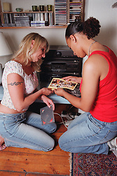 Lesbian couple kneeling on living room floor looking through compact disk collection,