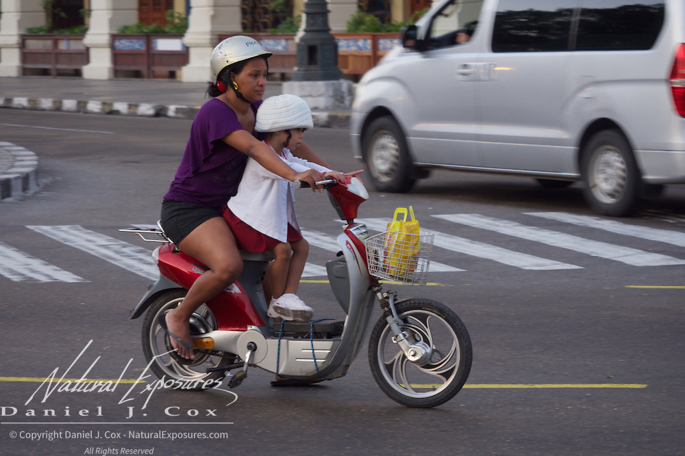 A woman and her child on a motorized scooter in Havana, Cuba