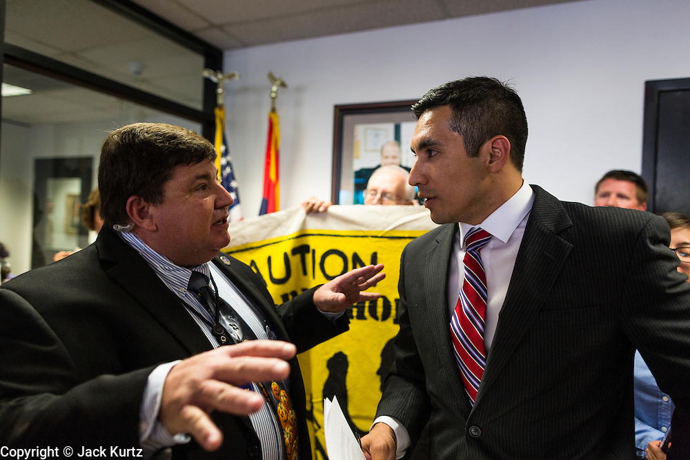 17 OCTOBER 2013 - PHOENIX, AZ:  CHARLES LOFTUS, left, from the office of the Arizona Attorney General, tries to talk to JOSE BETO SOTO, field director of Citizens for a Better Arizona shortly before having Soto arrested during a protest in the offices of Arizona Attorney General. About 100 people came to the office of Arizona Attorney General Tom Horne to protest the decision by Horne to sue community colleges in Maricopa County that charge DREAM Act students who are residents of Arizona out of state tuition rather than in state resident tuition. Nearly 10 people were arrested in a planned civil disobedience during the protest.     PHOTO BY JACK KURTZ