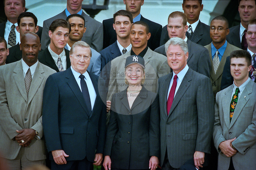 First lady Hillary Rodham Clinton, wearing a New York Yankees baseball cap and President Bill Clinton smile as they pose for a photo with Yankees owner George M. Steinbrenner III (L) and the team as the 1998 World Series winning Yankees visited the White House June 10, 1999 in Washington, DC.