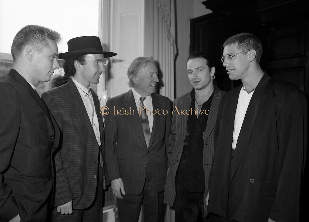 U2 Meet An Taoiseach, Charles Haughey.    (R58)..1987..18.05.1987..05.18.1987..18th May 1987..After their highly successful tour of America, An Taoiseach, Charles Haughey welcomed U2 back to Ireland with a reception held in Iveagh House, Dublin. Iveagh House formerly a home to the Guinness family is now held by the Department of Foreign Affairs...U2 and An Taoiseach pose for the cameras; (L-R),.Larry Mullen, 'The Edge' (Dave Evans),Charles Haughey, 'Bono' (Paul Hewson) and Adam Clayton.