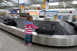 © licensed to London News Pictures. London, UK 08/04/2012. A child tying to grab a bag from a baggage dispenser at Stansted Airport, this afternoon (08/04/12) . Photo credit: Tolga Akmen/LNP