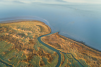 Aerial view of wetland near lake water during sunset, Netherlands.