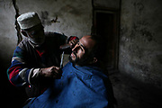Shar Jan, 53, at left, a barber works inside a hammam, a public shower, cuts the beard of Shokrullah, 50, a coal miner, at Karkar Coal Mine in north of Pul-e-Khomri, Baghlan province.