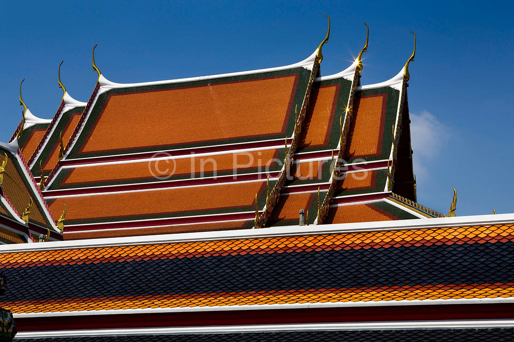 Coloured ceramic  tiles on the chedi roofs of Wat Pho temple, Bangkok. Wat Pho is one of the largest and oldest wats in Bangkok (with an area of 50 rai, 80,000 square metres), and is home to more than one thousand Buddha images, as well as one of the largest single Buddha images of 160ft length: the Reclining Buddha .