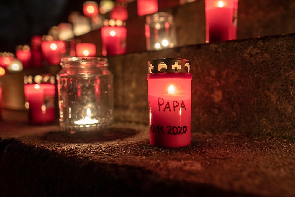 """A candle with the word """"PAPA"""" written on it burns at a makeshift memorial in Berlin, Germany, January 17,  2021. The memorial is part of the initiative  """"Corona-Tote sichtbar machen"""" (lit. Make corona deaths visible) by Christian Y. Schmidt and Veronika Radulovic,  since December 6, 2020, people gather at the fountain of Arnswalder Platz every Sunday at 16:00, light candles and place placards with the current death toll reported in Germany at the time. The death toll in Germany by variouse sources revolved around 47,000."""