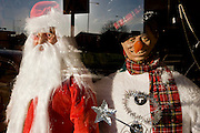 Santa and snowman Christmas party costumes are displayed in the front window of a fancy dress shop in Goven Hill, south Glasgow.