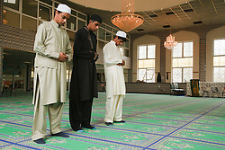 Muslim boys in stages of prayer in a Mosque.
