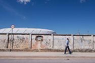 A man walks down the street opposite the newly built Arena da Amazonia visible over the crumbling wall, Manaus, Brazil, ahead of the England v Italy World Cup 2014 group match. Photo by Andrew Tobin/Tobinators Ltd