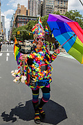 "New York, NY - 25 June 2017. New York City Heritage of Pride March filled Fifth Avenue for hours with groups from the LGBT community and it's supporters. A man in a costume covered in flowers with a sign that reads ""The Party's Here!"""