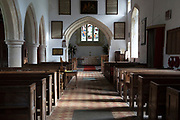 View past wooden pews to chancel arch and altar in sanctuary in the church at Milton Lilbourne, Wiltshire, England. The church was renovated in 1875, overseen by Reverend John Henry Gale vicar from 1846 until 1893.