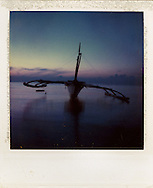 Traditional pump boat anchored in calm waters near shore at dawn, Palawan Island, Philippines, Southeast Asia