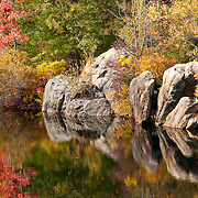Boulders on the shore of Pearce Lake, with fall colors, in Breakheart Reservation, Wakefield, Massachusetts