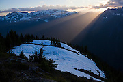 The setting sun casts a shaft of light over the ridge dividing Bacon Creek with North Cascades National Park, Washington.