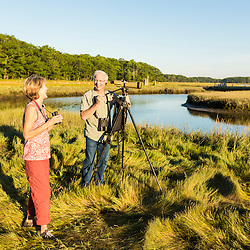 A couple bird watching on a salt marsh at the Brave Boat Harbor Headwaters preserve in Kittery, Maine.