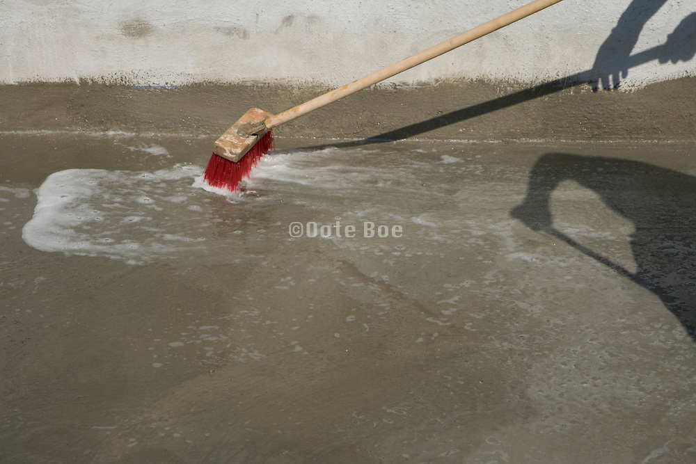 with a broom getting water of concrete floor