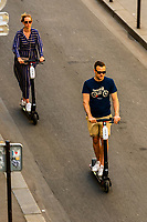 People riding electric scooters down Rue St. Dominique, Paris, France.