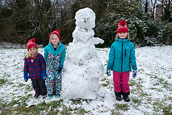 © Licensed to London News Pictures; 24/01/2021; Bristol, UK. PHOEBE CONRAD age 3, THEA CONRAD age 5, ROSA CONRAD age 7 pose with the snowman they built. People exercise and enjoy some snow at Brandon Hill by sledging and building snowmen as England is under a third national lockdown since the start of the Covid-19 coronavirus pandemic after a new strain of a more infectious Covid virus has spread through the country. Photo credit: Simon Chapman/LNP.