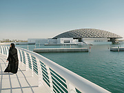 A woman wearing traditional Hijab walks along the water next to the Louvre Abu Dhabi, an art and civilization museum designed by famous architect Jean Nouvel.