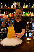Flushing, NY - December 16, 2016. The Coop's bartender, Ava Choi, and a mango soju cocktail.