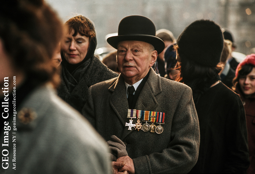 Elderly man, coat adorned with military medals, attends funeral.
