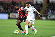Jefferson Montero of Swansea city goes past QPR's Nedum Onuoha. Barclays Premier league match, Swansea city v Queens Park Rangers at the Liberty stadium in Swansea, South Wales on Tuesday 2nd December 2014<br /> pic by Andrew Orchard, Andrew Orchard sports photography.