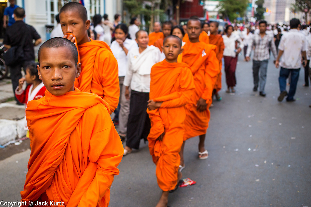 """03 FEBRUARY 2013 - PHNOM PENH, CAMBODIA:   Novice Buddhist monks walk down the street to the final Buddhist chanting service for former Cambodian King Norodom Sihanouk in the crematorium built for the King's funeral at the National Museum in Phnom Penh. Norodom Sihanouk (31 October 1922- 15 October 2012) was the King of Cambodia from 1941 to 1955 and again from 1993 to 2004. He was the effective ruler of Cambodia from 1953 to 1970. After his second abdication in 2004, he was given the honorific of """"The King-Father of Cambodia."""" He served as puppet head of state for the Khmer Rouge government in 1975-1976, before going into exile. Sihanouk's actual period of effective rule over Cambodia was from 9 November 1953, when Cambodia gained its independence from France, until 18 March 1970, when General Lon Nol and the National Assembly deposed him. Upon his final abdication in 2004, the Cambodian throne council appointed Norodom Sihamoni, one of Sihanouk's sons, as the new king. Sihanouk died in Beijing, China, where he was receiving medical care, on Oct. 15, 2012. His cremation will take place on Feb. 4, 2013. Over a million people are expected to attend the service.   PHOTO BY JACK KURTZ"""