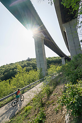 Mature biker riding bike on road below elevated road