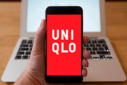 Using iPhone smartphone to display logo of Uniqlo , the Japanese casual wear designer, manufacturer and retailer