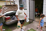 (MODEL RELEASED IMAGE). The Browns return from the grocery store to their modest neighborhood in Riverview, outside of Brisbane, Australia. Hungry Planet: What the World Eats (p. 26).