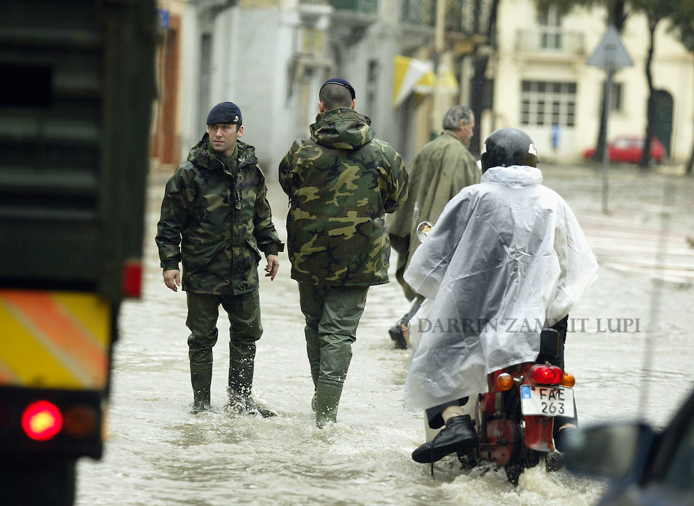 Soldiers attempt to divert traffic away from flooded areas  in the town of Msida, outside Valletta, November 6, 2002.  Heavy rainfall caused widespread flooding and damage throughout the Maltese islands, though no serious injuries were reported...MALTA OUT..REUTERS/Darrin Zammit Lupi