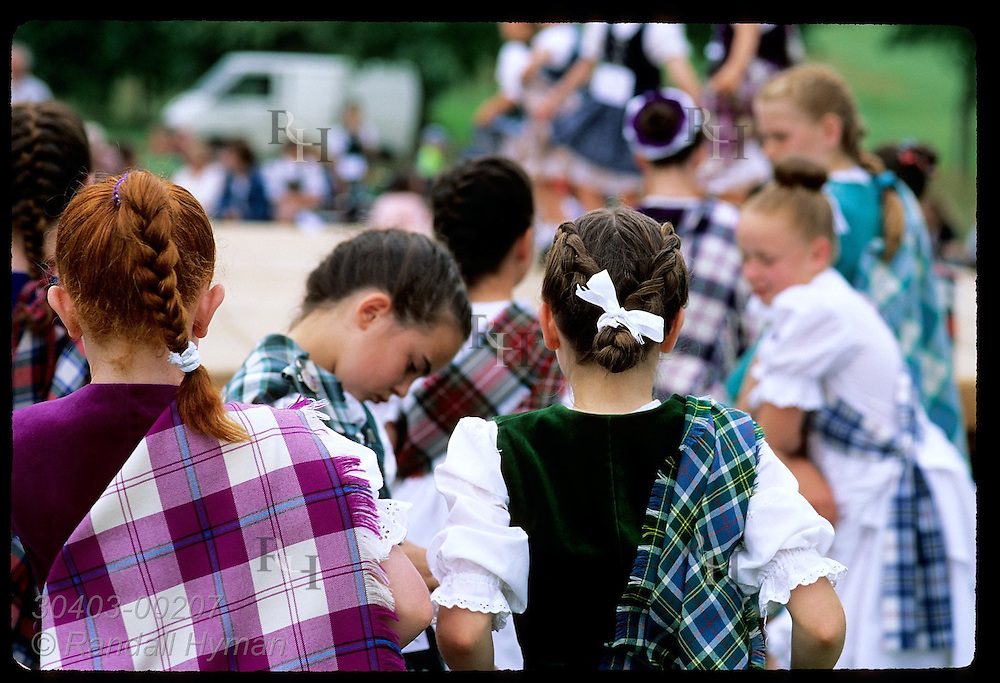 Girls in tartans & finery wait to mount stage at Highland dance contest; Stirling Highland Games Scotland