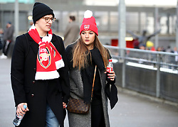 Arsenal fans arrive at the stadium before the match begins