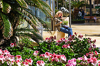 Avenida del Mar, Marbella, Spain, girl on mobile phone, 14th April 2018, 201804144294<br /> <br /> Copyright Image from Victor Patterson, 54 Dorchester Park, Belfast, UK, BT9 6RJ<br /> <br /> t1: +44 28 9066 1296 (from Rep of Ireland 048 9066 1296)<br /> t2: +44 28 9002 2446 (from Rep of Ireland 048 9002 2446)<br /> m: +44 7802 353836<br /> <br /> e1: victorpatterson@me.com<br /> e2: victorpatterson@gmail.com<br /> <br /> The use of any of my copyright images is subject to my Terms & Conditions. It is IMPORTANT that you familiarise yourself with them. They are available at my website, victorpatterson.com.<br /> <br /> None of my copyright images may be used on the Internet unless they are visibly watermarked, i.e. © Victor Patterson within the body of the image. My metadata, denoting my copyright must NOT be deleted. <br /> <br /> Web use is extra at currently recommended NUJ rates. Maximum permitted web size is<br />  400kb. <br /> <br /> Images must not be passed on to a third party - they are for the use of the authorised recipient only.